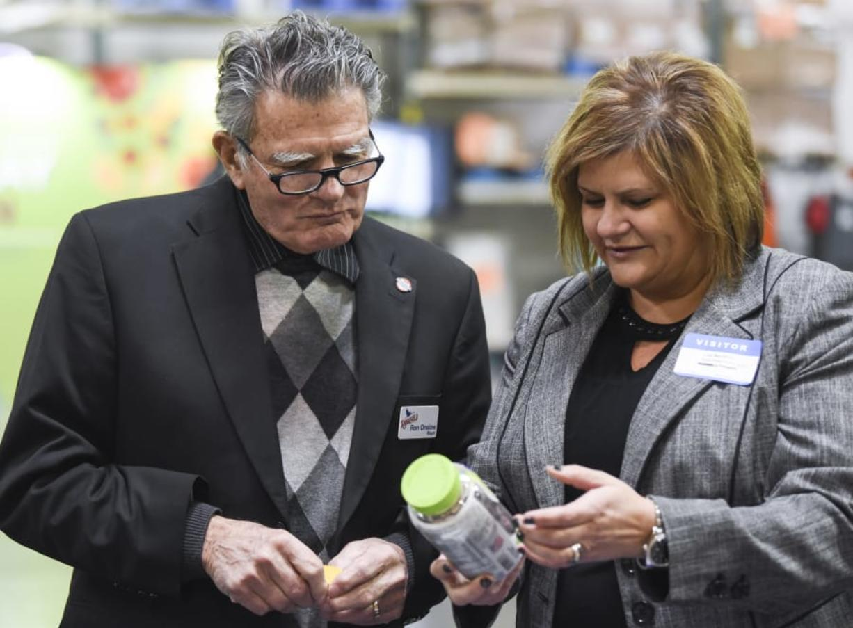 Ridgefield Mayor Ron Onslow looks at a bottle of Vitafusion chewable vitamins with Church & Dwight Co. Inc. Vice President of Sales Lisa MacMillin on Dec. 14, at an event in Vancouver. Onslow is stepping down as mayor after 10 years in office.