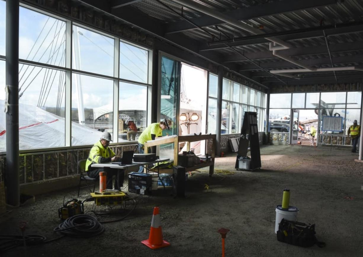 Terry Koker, left, and Brandon Koumaros of R. Miller Construction look over plans for WildFin American Grill inside the restaurant. The restaurant officially took occupancy Monday at The Waterfront Vancouver. It is expected to open in August.