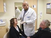 Neurologist Gurjeet Singh injects Botox into Kari Carlson's forehead as her husband, Keith Carlson, offers his support. Carlson receives 31 Botox injections every 12 weeks to manage her chronic migraines.