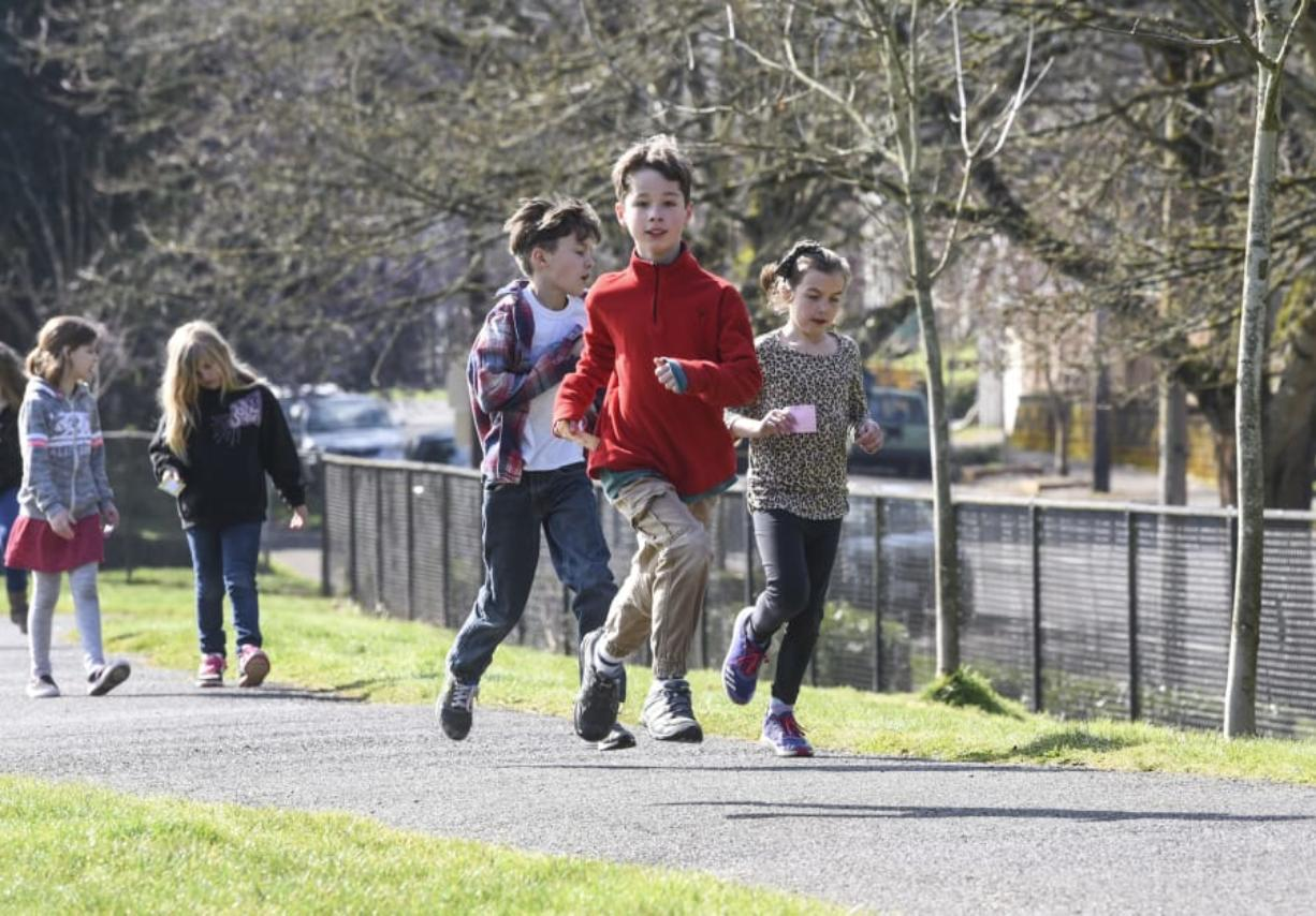 Third-graders Avery Ahrens, from left, Sam Coté and Karina Woodley run laps around the playground at Hough Elementary School. The trio are among the regular participants in the new Hough Mileage Club — a voluntary running program offered during lunch recesses. (Ariane Kunze/The Columbian)