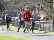 Third-graders Avery Ahrens, from left, Sam Coté and Karina Woodley run laps around the playground at Hough Elementary School. The trio are among the regular participants in the new Hough Mileage Club — a voluntary running program offered during lunch recesses.