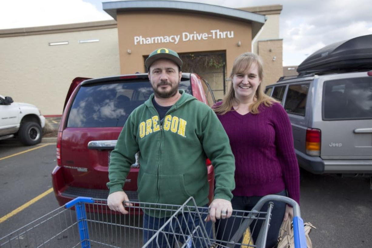 Chris and Jennifer Waller stand in the Walmart parking lot in Battle Ground after a shopping trip. The family is one of many in Clark County who earn below the median wage and have not seen wages rise even as the economy as thrived.