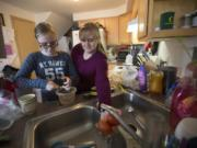 Jennifer Waller, right, prepares guacamole with daughter Kayla, 13, at their Battle Ground home. The family earns just below the median wage in Clark County but relies heavily on government programs such as food stamps and Women, Infants and Children to pay for groceries.