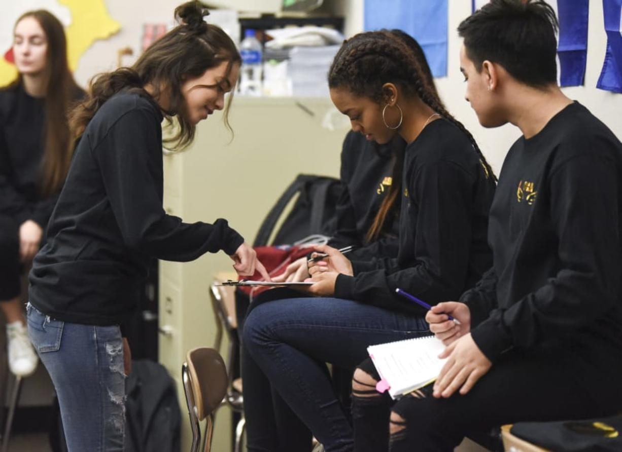 Evergreen High School student Samantha Robles, left, reviews lines and stage directions with Reymi Shelton and Jesus Coronel from their script. As far as anyone knows, Friday night's performance will be the first Spanish-language play staged by the Evergreen School District. (Ariane Kunze/The Columbian)