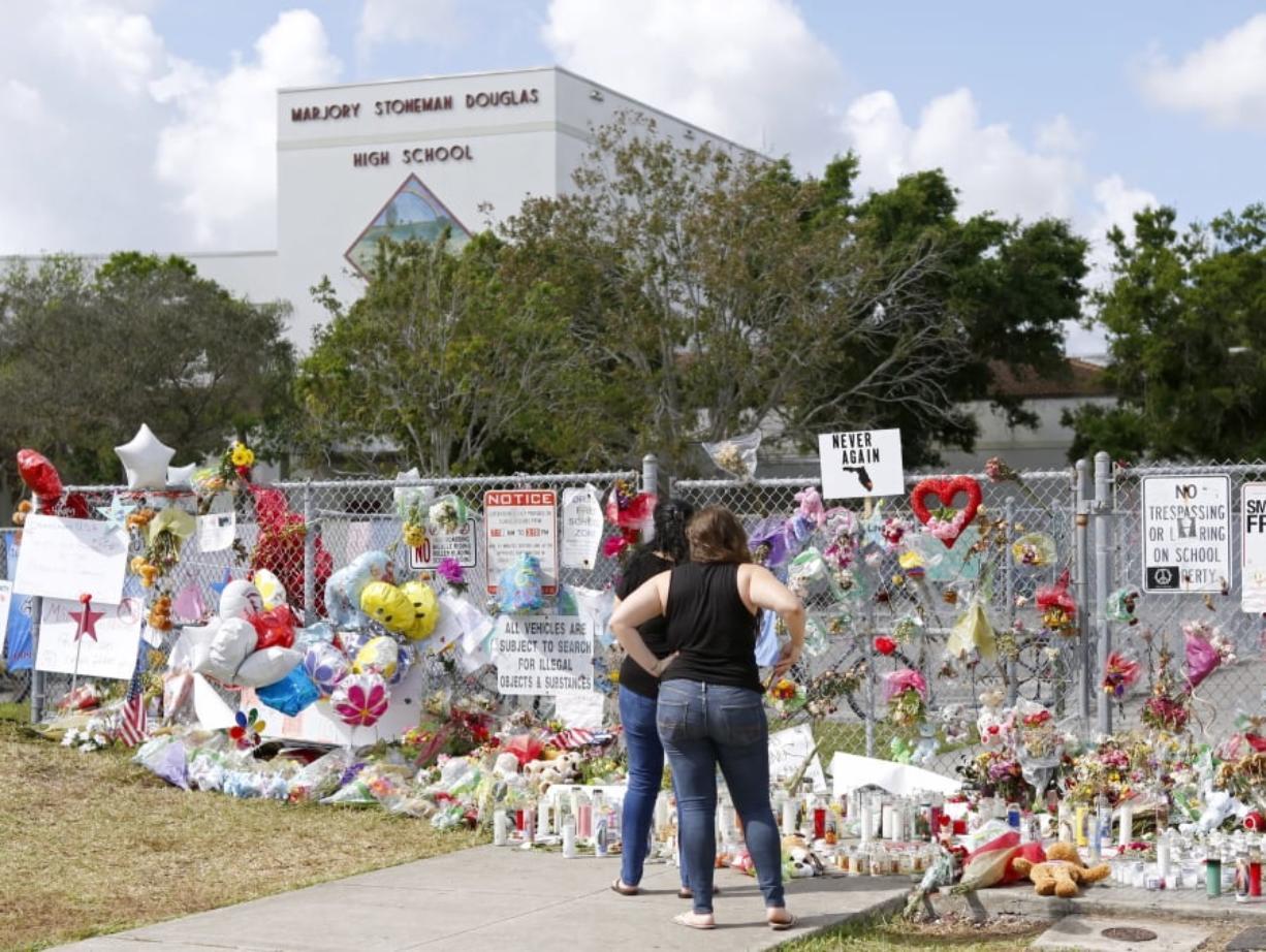 A memorial for the victims of the Feb. 14 shooting lines a fence at Marjory Stoneman Douglas High School in Parkland, Fla.