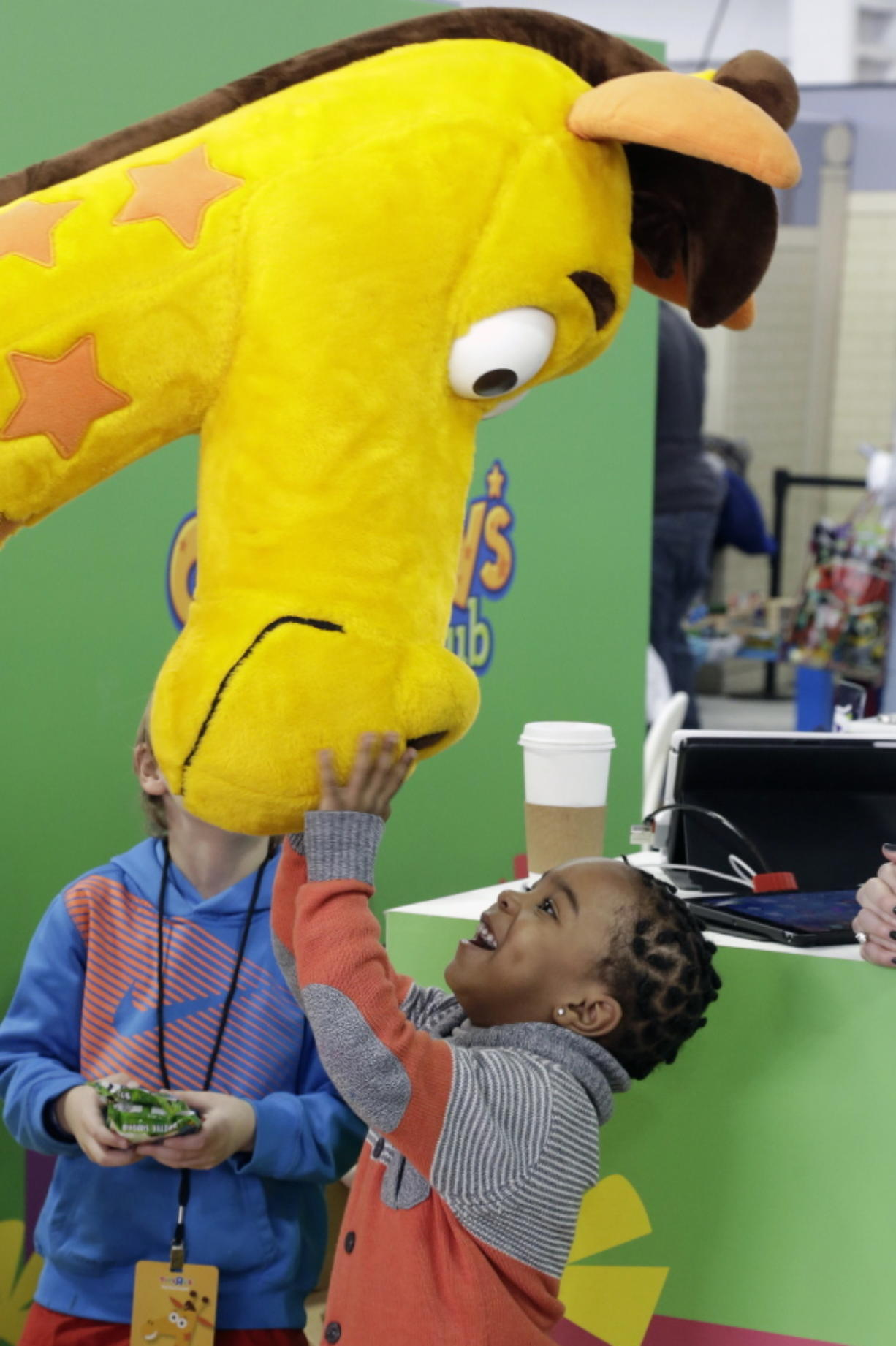 Jahmae Evans, 4, talks to Geoffrey the Giraffe — the corporate symbol for Toys R Us since 1965 — at the 2016 Toy Fair in New York.
