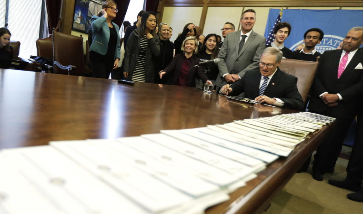 A long line of bills are placed on a table in the Governor's conference room at the Capitol in Olympia on Wednesday. Ted S.