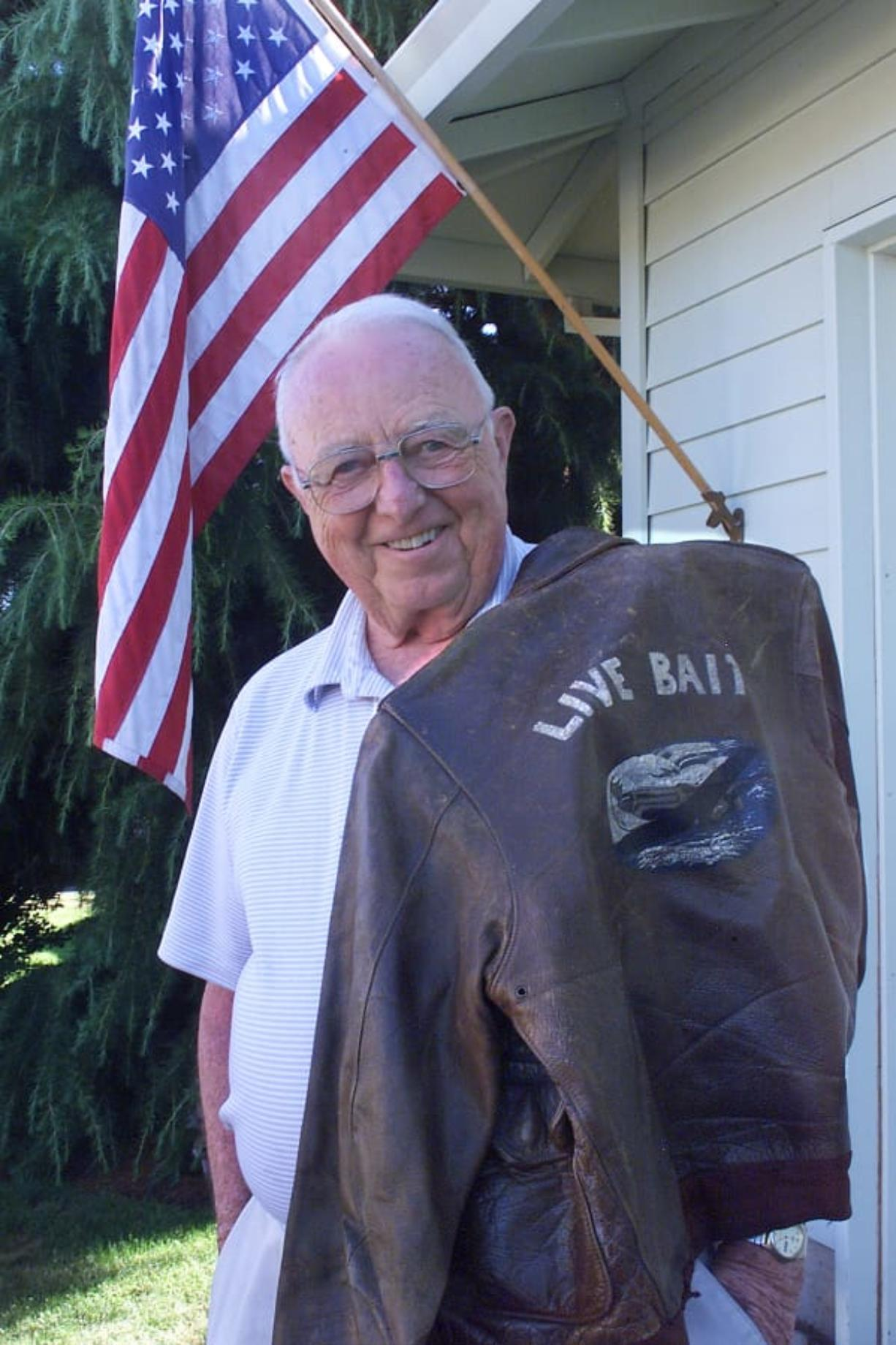 """Clayton Kelly Gross drapes his """"Live Bait"""" flight jacket over his shoulder in a 2002 photograph. The jacket is now in the National WWII Museum."""