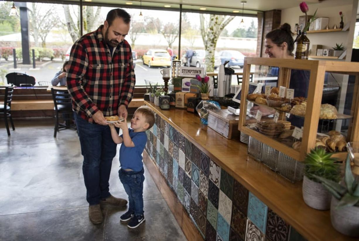 After closing up shop on Devine Road in June, River Maiden Artisan Coffee is back up and running at a new location — 5301 E. Mill Plain Blvd. — in Vancouver. Adam Hendrix of Vancouver, left, and his son, Cal, 3, stop by the new shop for a treat on Monday morning.