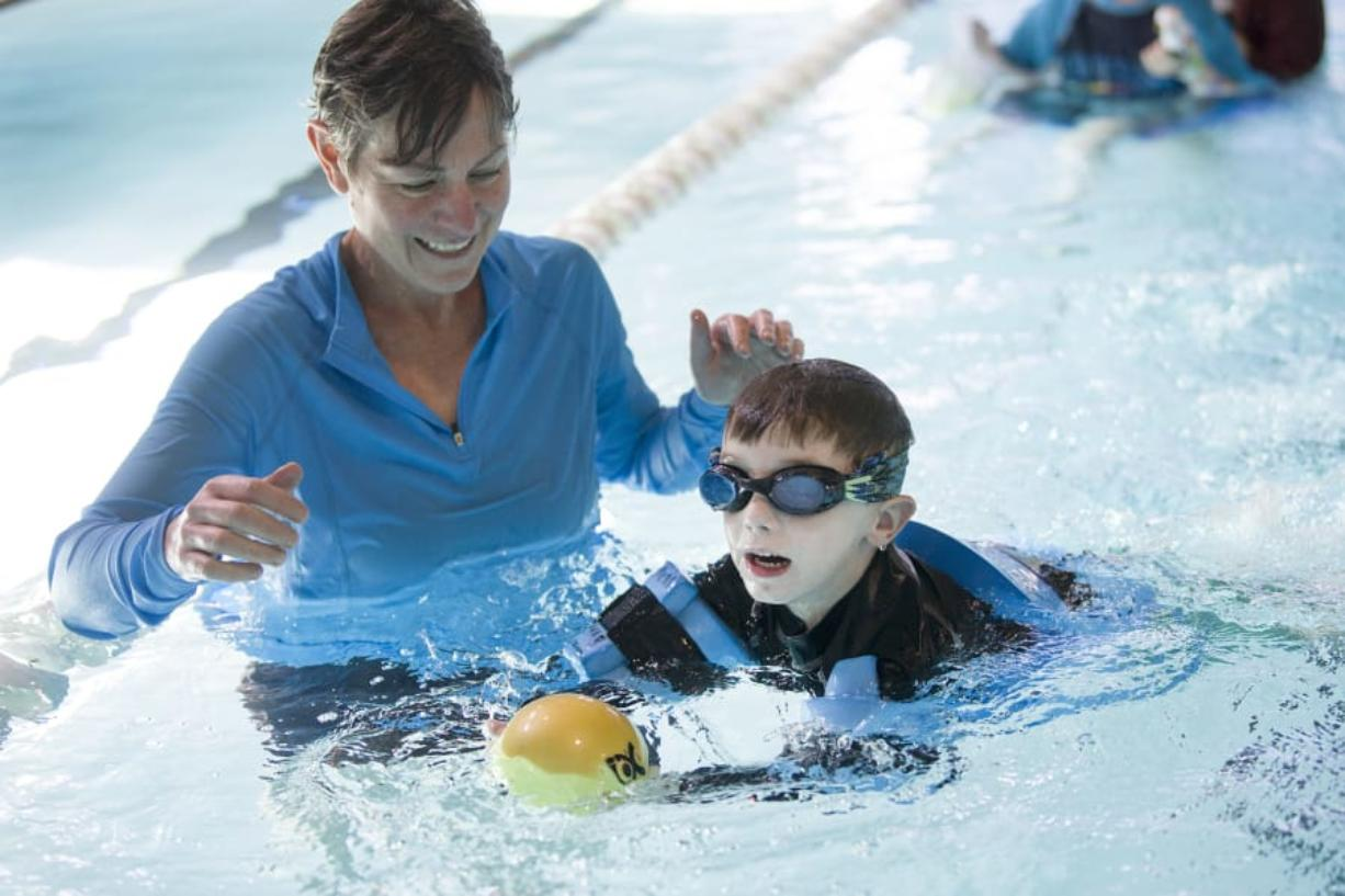 Occupational therapist Karen Drogos, left, helps Gary Silvas, 5, swim to capture a ball during a water-based physical therapy session at the Marshall Center. Gary was a micro-preemie and weighed just 1 pound, ½ ounce at birth. Photos by Ariane Kunze/The Columbian