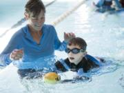 Occupational therapist Karen Drogos, left, helps Gary Silvas, 5, swim to capture a ball during a water-based physical therapy session at the Marshall Center. Gary was a micro-preemie and weighed just 1 pound, ½ ounce at birth.