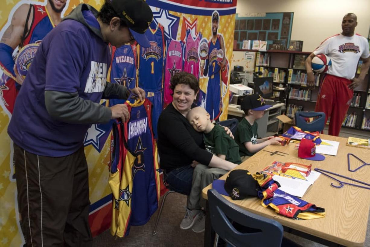Manu Iyer, with the Harlem Wizards, presents Lauren Reagan with team jersey for her and her husband, Francis Reagan. Their twin sons, Declan and Adrian, were signed by the team during a ceremony Wednesday morning. Declan recently started hospice care after a two year fight with leukemia.