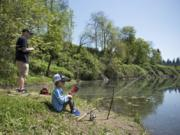 Adam Resendiz of Vancouver, left, and his son Abraham, 4, fish together at Klineline Pond in Vancouver on Wednesday afternoon, April 25, 2018. Resendiz said he started fishing around Abraham's age, so he enjoys watching him learn. Temperatures reached record-breaking numbers in the low 80s this week, but are predicted to fall back to the 50s on Friday.