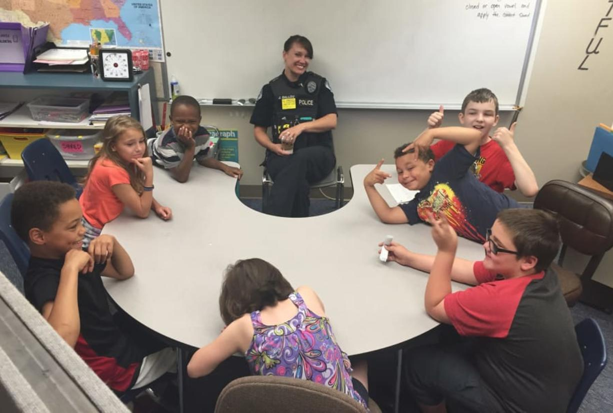 "Vancouver police officer Julie Ballou sits with a group of fifth-graders at Orchards Elementary School. As part of her volunteering work with the Police Activities League, Ballou ""adopted"" the class, and meets with them regularly. (Courtesy of Julie Ballou)"