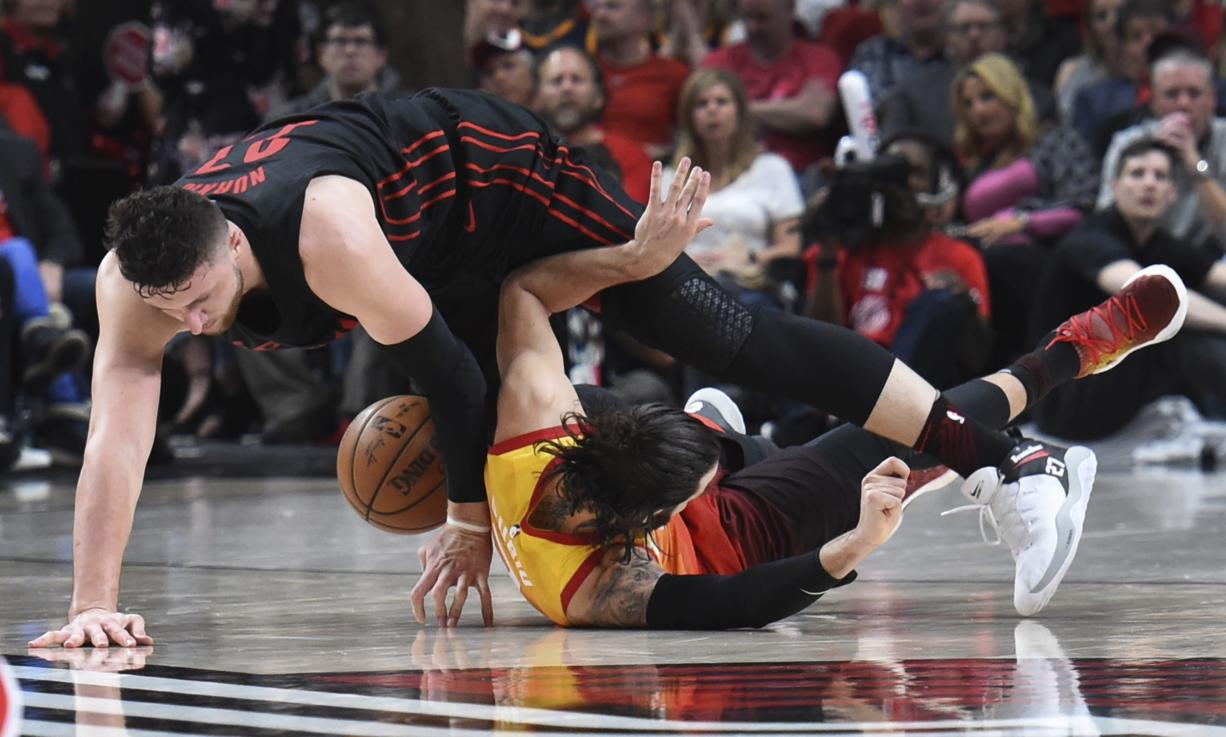 Portland Trail Blazers center Jusuf Nurkic, top, and Utah Jazz guard Ricky Rubio scramble for a ball during the second half of an NBA basketball game in Portland, Ore., Wednesday, April 11, 2018. The Blazers won 102-93.