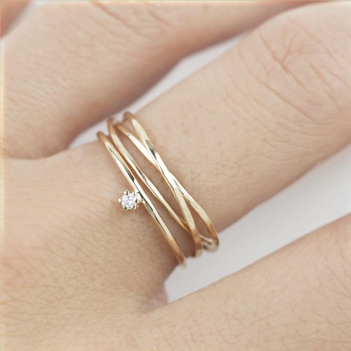 Envero Jewelry's delicate set of hand-hammered trinity rings, and a 14K gold band with solitaire diamond. The piece reflects a trend toward unique modern bridal jewelry.