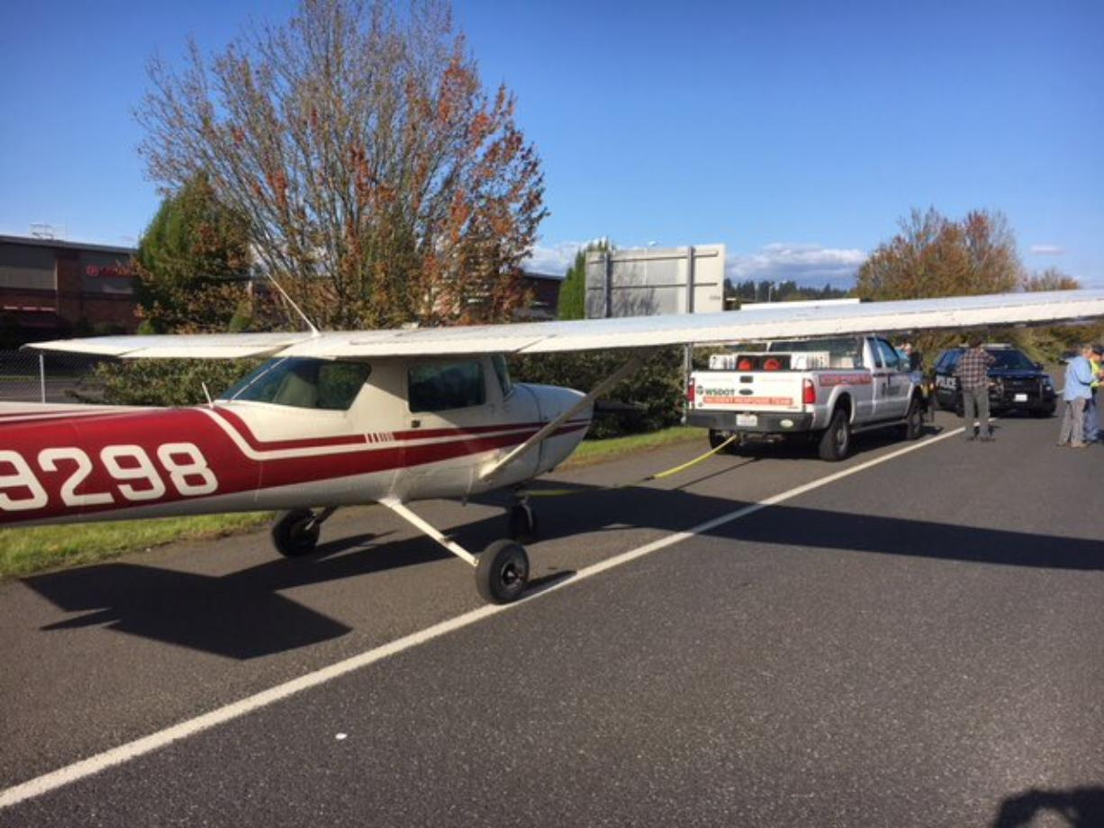 A Washington Department of Transportation emergency response team prepares to tow a single-engine aircraft that landed on state Highway 14 on Saturday afternoon. No injuries were reported.