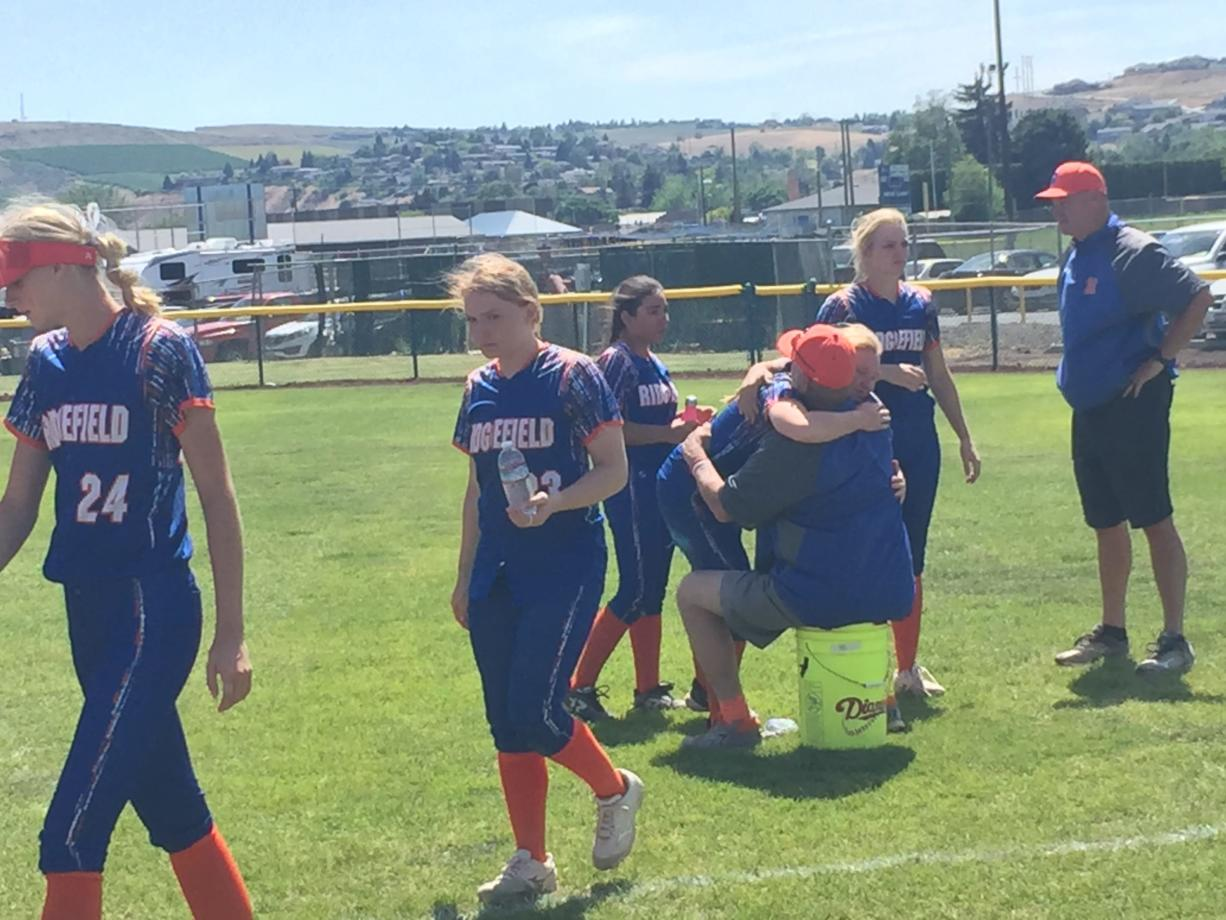 Ridgefield softball players hug coach Dusty Anchors after the team's season ended Saturday at the Class 2A state tournament in Selah.