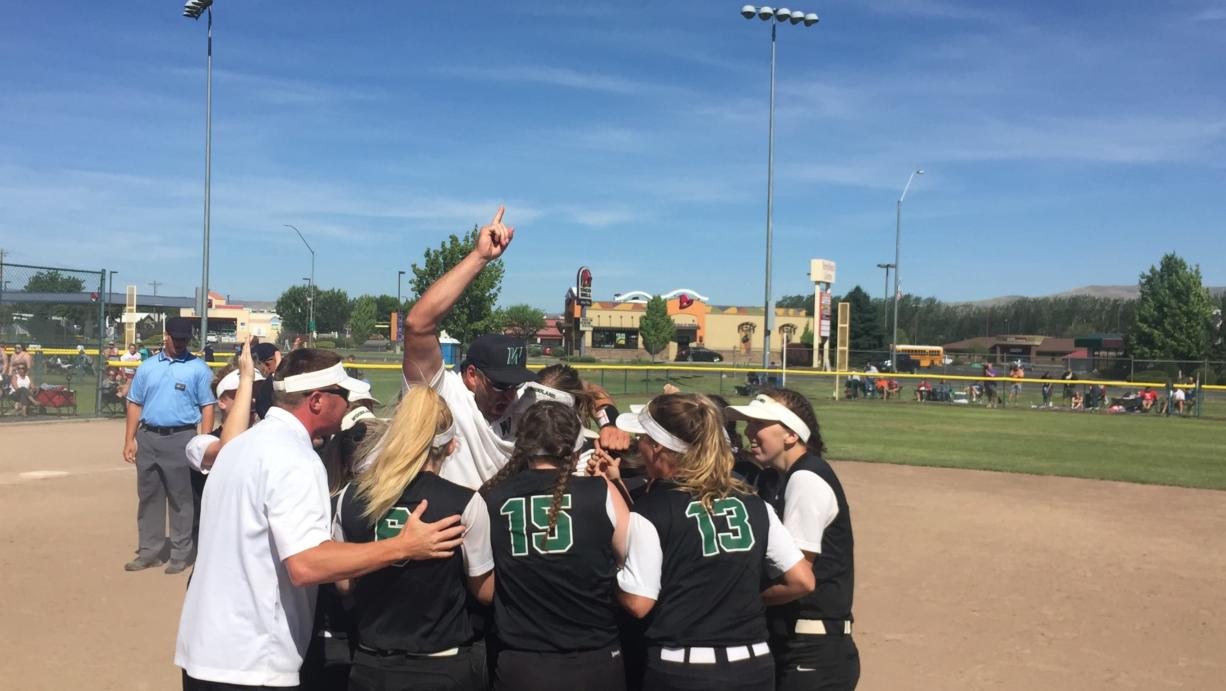 The Woodland softball team swarms around coach Tom Christensen after winning the Class 2A state softball championship Saturday in Selah.