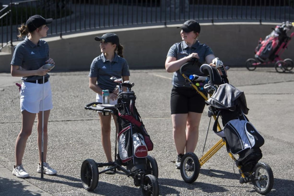 Woodland Middle School eighth-grader Katherine Patnode, left, seventh-grader Lucy Sams, center, and seventh-grader Maryjane Moss, right, wait to tee off during their match against Columbia River High School at Lewis River Golf Course on Thursday, April 26, 2018. (Alisha Jucevic/The Columbian)