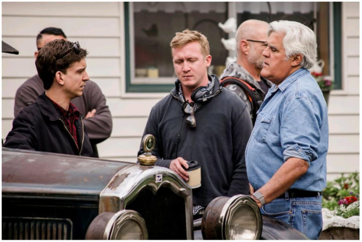 Clayton Paddison, left, a crew member and Jay Leno consult during filming at Paddison's home on Wednesday morning.