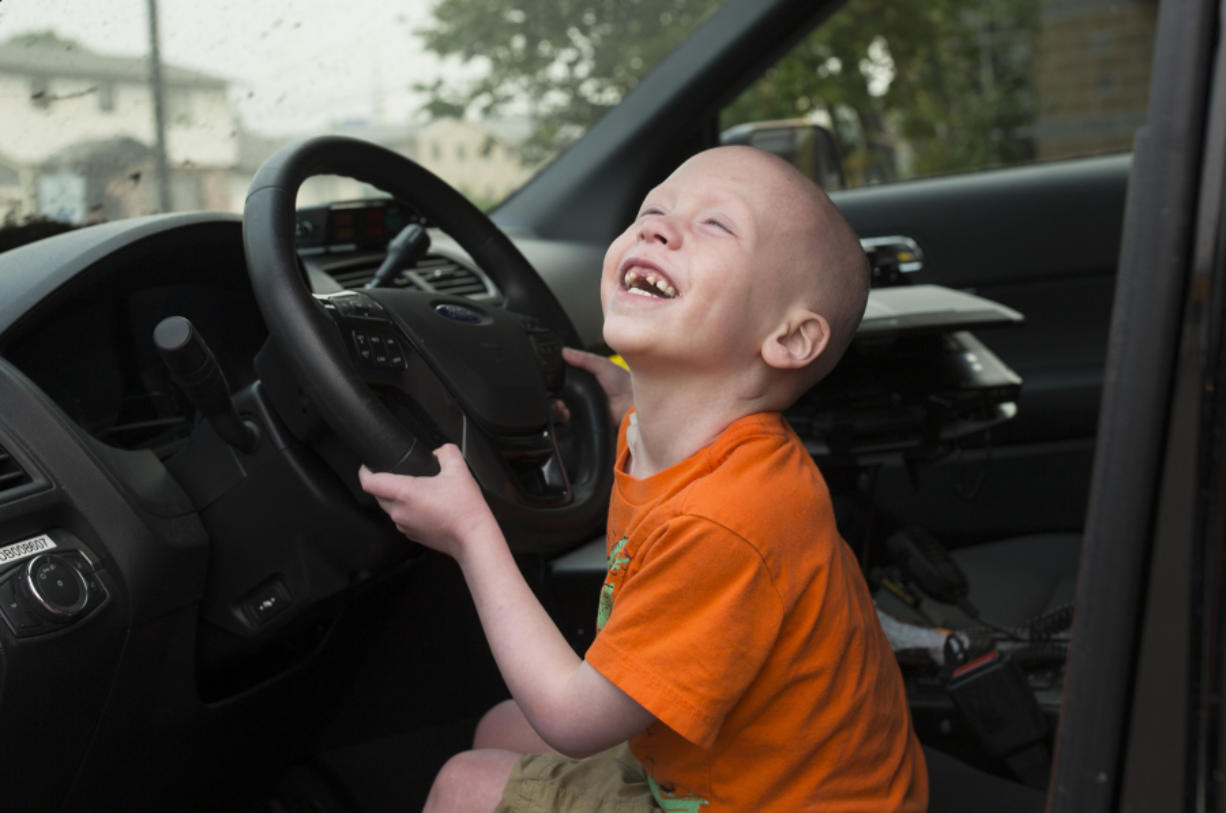 Declan Reagan plays inside his dad's police cruiser at the Washougal Police Department in Washougal in 2017. A woman from England had donated her bone marrow for his transplant. He died Friday. The Columbian files