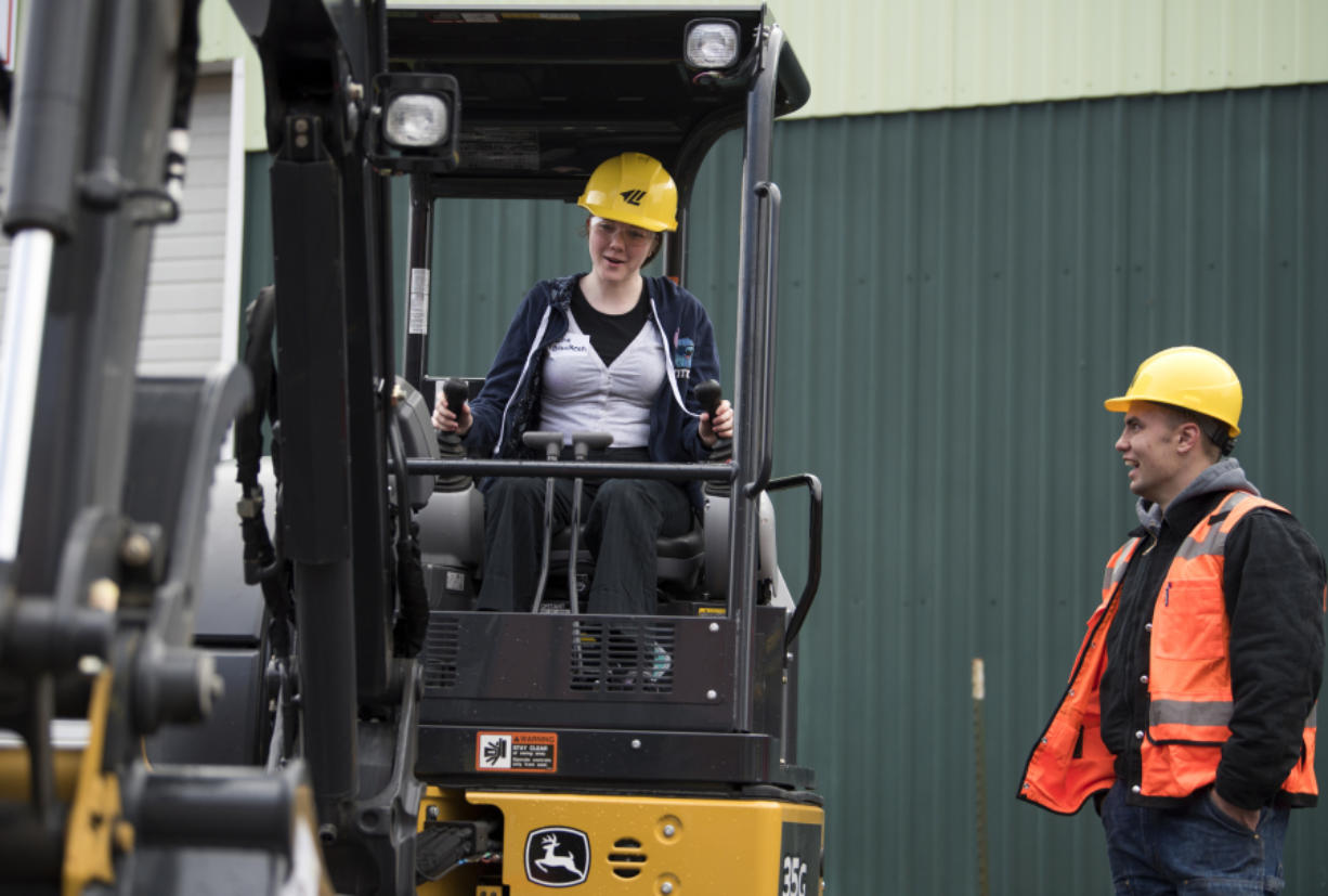 CAM Academy freshman Sadie Brackeen, left, learns to operate an excavator at the Youth Employment Summit in April. More than 700 students could meet with 30 companies there that have many job openings in today's growing economy. (Alisha Jucevic/The Columbian)