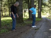 Richard Landis, left, and Bernie Ritter discuss damage to their road, Northeast 312th Avenue, and the recent efforts by Clark County to repair it. The residents say their one-lane road is getting perpetually damaged by the increased traffic relating to a new subdivision being built at the end of the road.