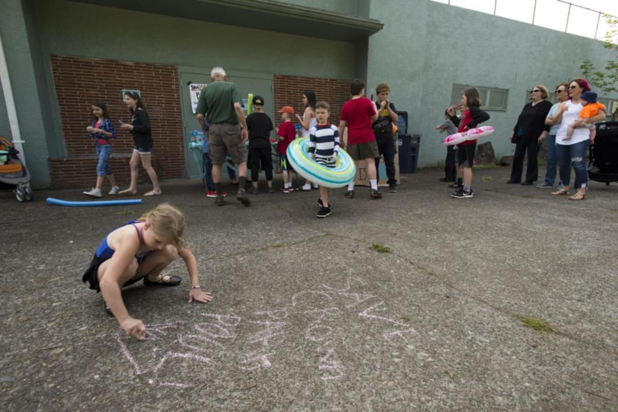 """The Friends of Crown Park Pool held a """"pool party without the pool"""" to try to save the Crown Park swimming pool, which is scheduled for demolition this fall. Elina Sams, 8, of Camas, and other kids wrote messages in chalk in support of the pool during the party."""