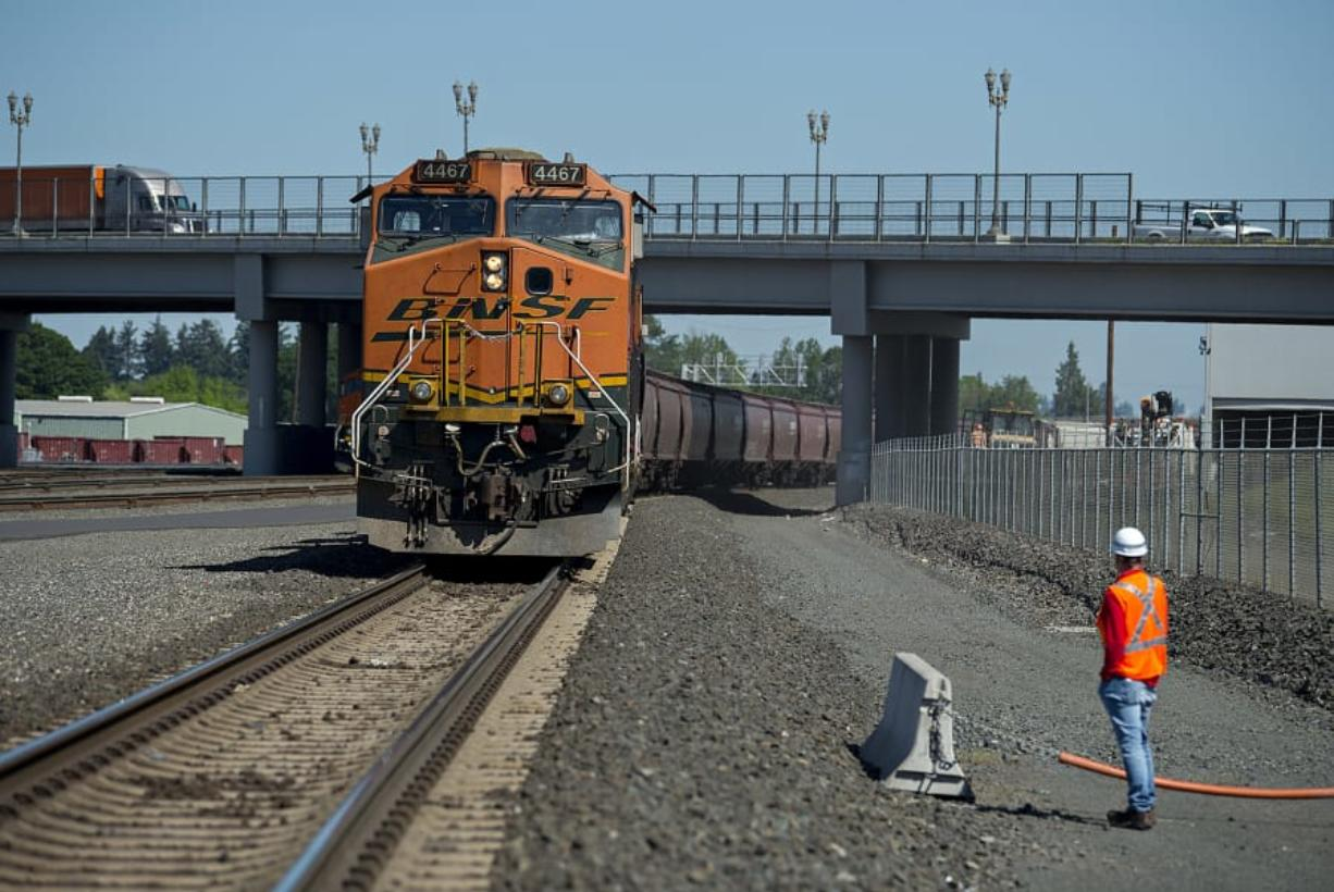 BNSF Railway spokesman Gus Melonas pauses to look over a train hauling grain as it is parked in BNSF's Vancouver yard last week. BNSF reported that it moved a record volume of material in the first quarter of this year.