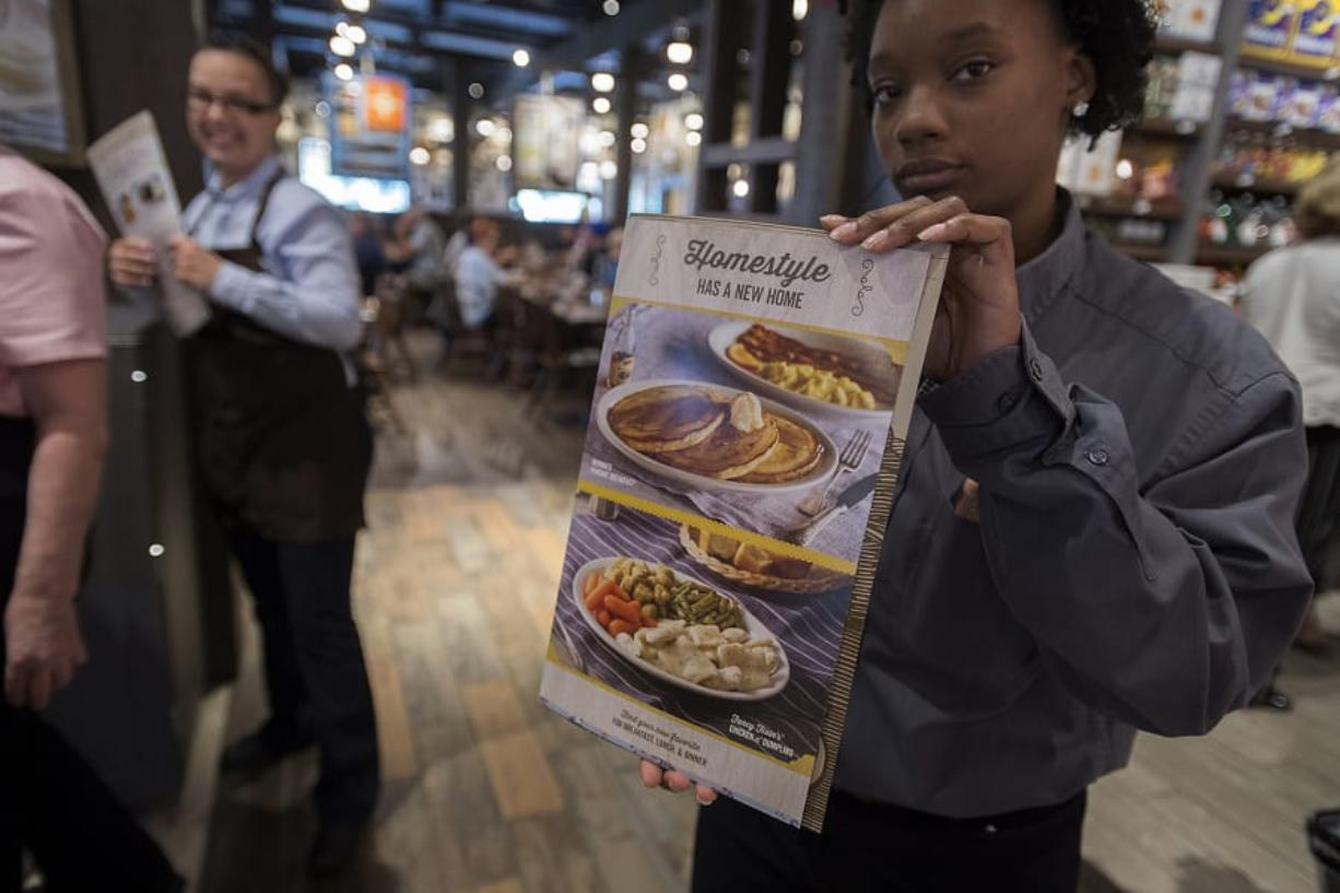 Operations trainer Nicole Brown displays a menu at the entrance to the dining area at Cracker Barrel Old Country Store. The store opened Monday and seats about 180.