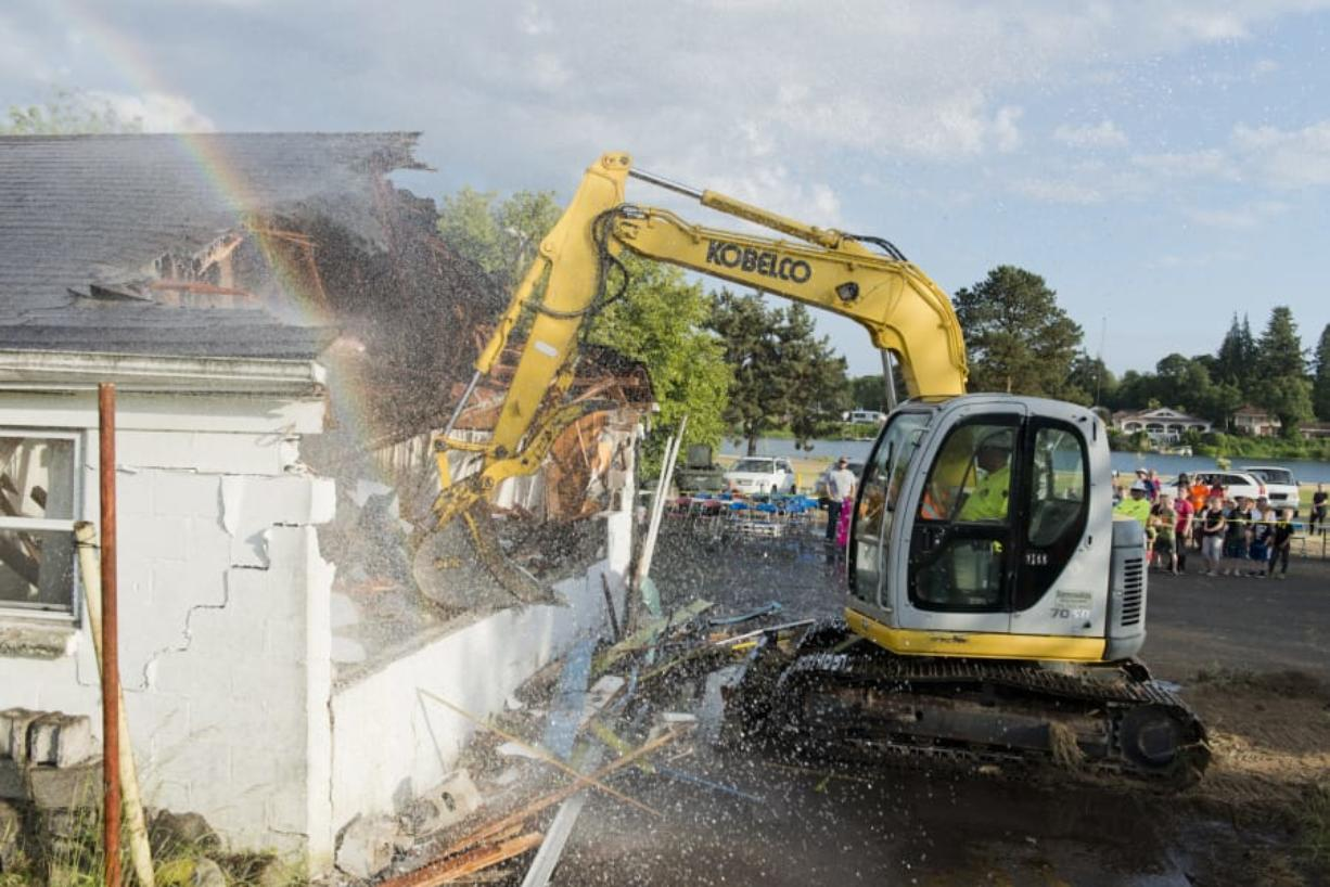 West Coast Training excavator operator Josh McClure demolishes one of the rooms at the defunct Lakeside Motel, where the Woodland Community Swimming Pool Committee plans on building a YMCA, with construction expected to start in 2020. Cowlitz Fire District No. 1 and Woodland Fire Department sprayed water on the motel to keep dust and lead paint particles down.