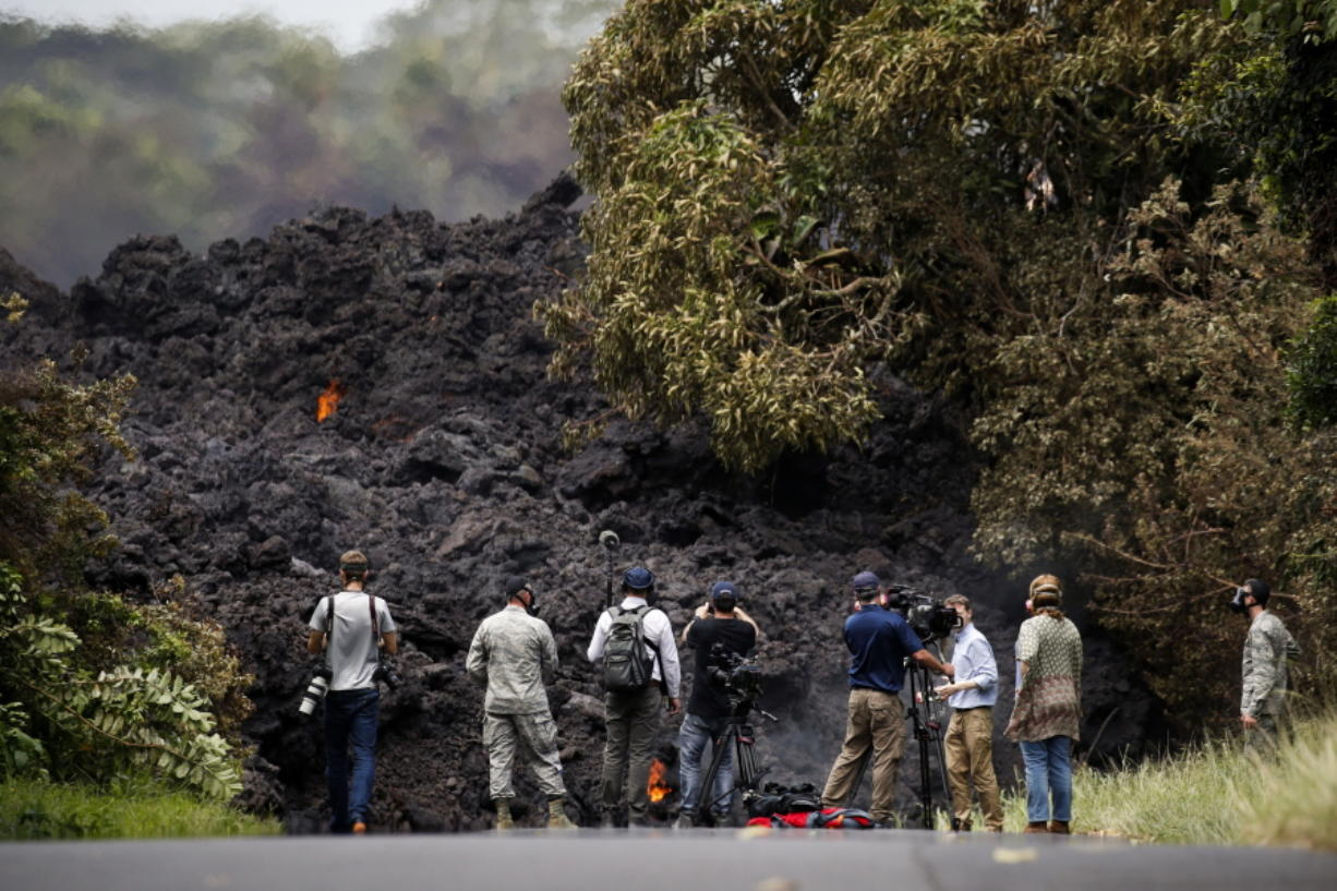 Members of the media record a wall of lava entering the ocean near Pahoa, Hawaii, on Sunday. Kilauea volcano, oozing, spewing and exploding on Hawaii's Big Island, has gotten more hazardous in recent days, with rivers of molten rock pouring into the ocean and flying lava causing the first major injury. (AP Photo/Jae C.