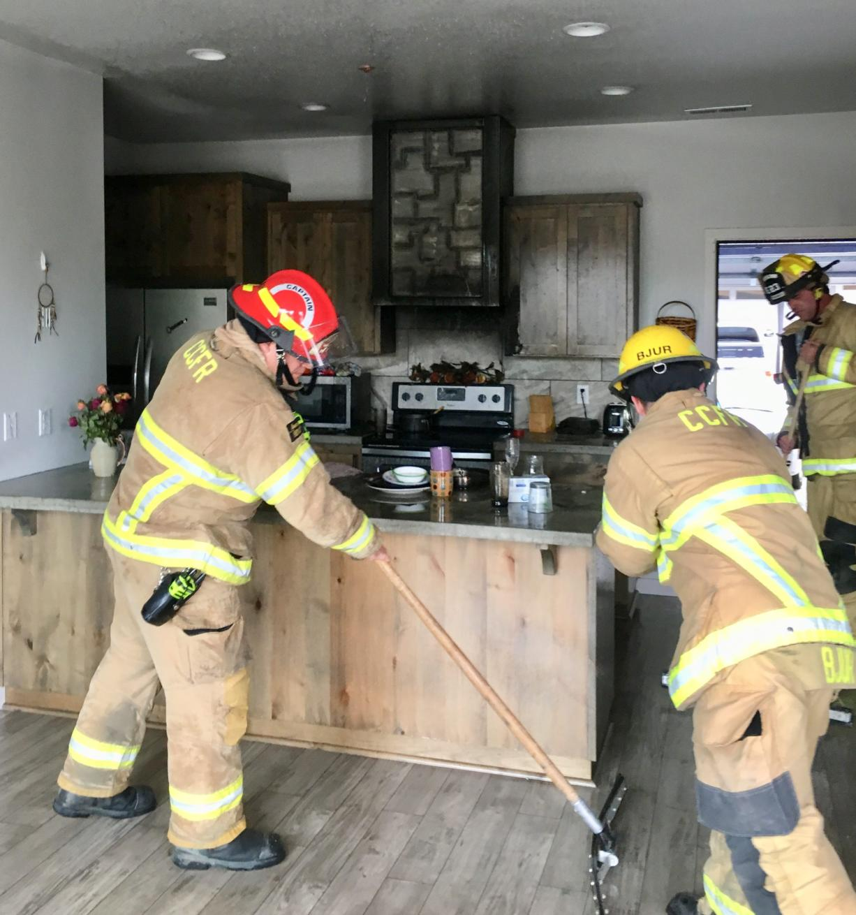 Firefighters clean up after a cooking fire Thursday morning at a Ridgefield condominium. The blaze was contained by a fire sprinkler system.