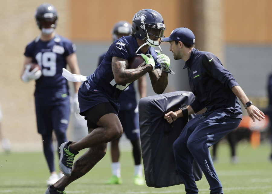 3bee1d675 Seattle Seahawks wide receiver Brandon Marshall, center, runs a drill  during NFL football practice