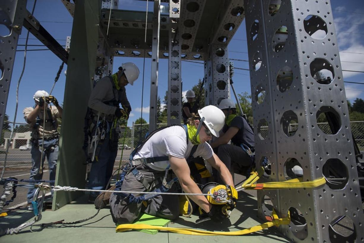 Student Justin Spencer, center in white, performs a simulated rescue while on a wind turbine training tower at the Northwest Renewable Energy Institute. Safety is a focus of student training.