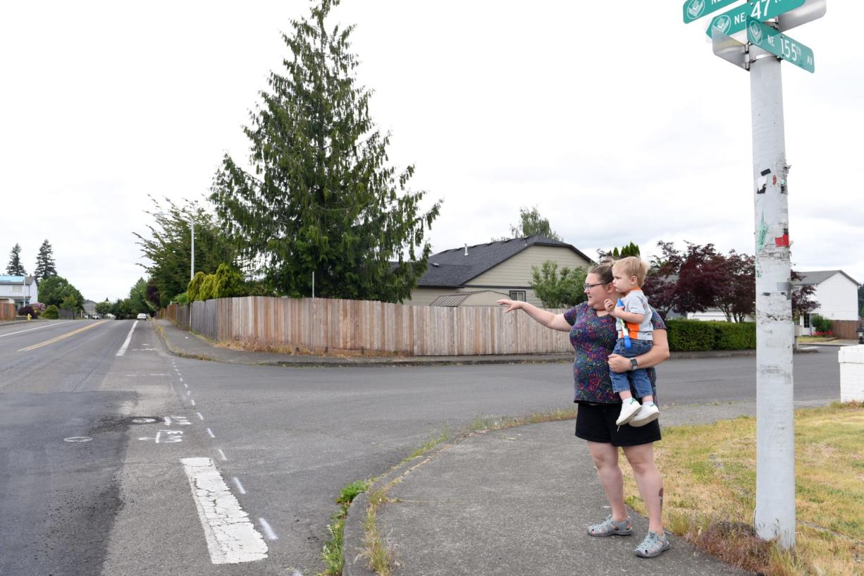 Heather Sinnott, chairwoman of the Burnt Bridge Creek Neighborhood Association, stands with her 2-year-old son, Henry, as she points to the intersection near her home on Northeast Poplar Street where the neighborhood association is hoping to paint a mural to slow down traffic. The speed limit where Poplar Street turns into Northeast 47th Street is 25 mph, but Sinnott says many drivers far exceed this speed and that it is dangerous for the neighborhood.