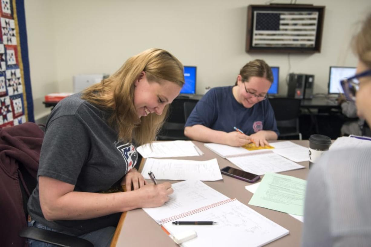 Alison Warlitner, from left, studies with friends Ashley Hopkins and Terri Vanderweide at the Clark College Veterans Resource Center on June 5. Warlitner is a Navy veteran and reservist who says she appreciates how the center supports her and her classmates.