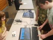 Alina Shcherbakova watches as Joshua Hill plays a video game she created during the school year. Video games and digital apps were on display Saturday at Cascade Park Community Library during Evergreen Public Schools Game Design Expo.