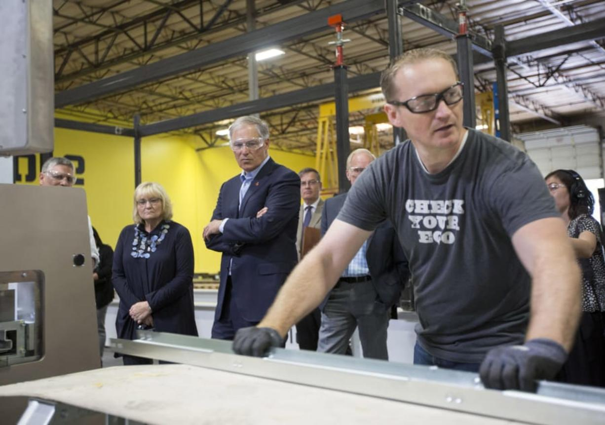 Gov. Jay Inslee, center, watch as Bryan Parmenter explains part of the production process at Blokable's Vancouver plant. The company has its first modular housing units coming online this summer. Photos by Natalie Behring for The Columbian