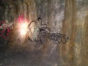 Graffiti that was sprayed inside the Ape Cave about two years ago is still on the wall. Forest Service officials say they're still searching for solvents that won't damage the cave's fragile environment.