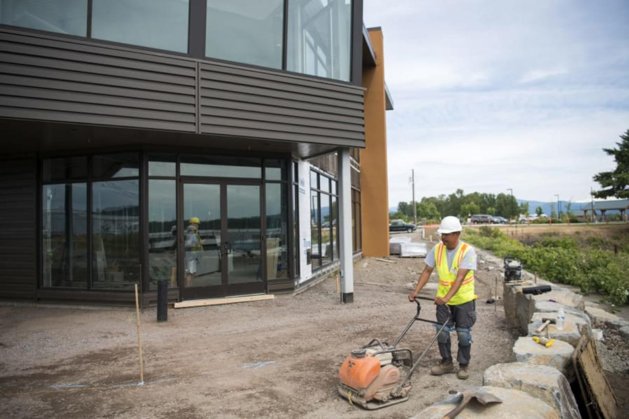 Efren Martinez Zavala with GRO Outdoor Living works on the outdoor patio outside The Black Pearl in Washougal. The long-unused building is expected to open as an events center in August.