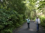 Vancouver residents Alice Perry Linker, left, and Fred Suter discuss what the forest between Moulton Falls and Lucia Falls parks might look like after timber is harvested in the area. The Washington Department of Recreation is planning the Michigan Trotter Timber Sale for January, which includes trees along 2,500 feet of the trail.