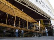 Plane builders and Fort Vancouver staff members ease the Curtiss Pusher into the Pearson Air Museum at Fort Vancouver National Historic Site on Tuesday.