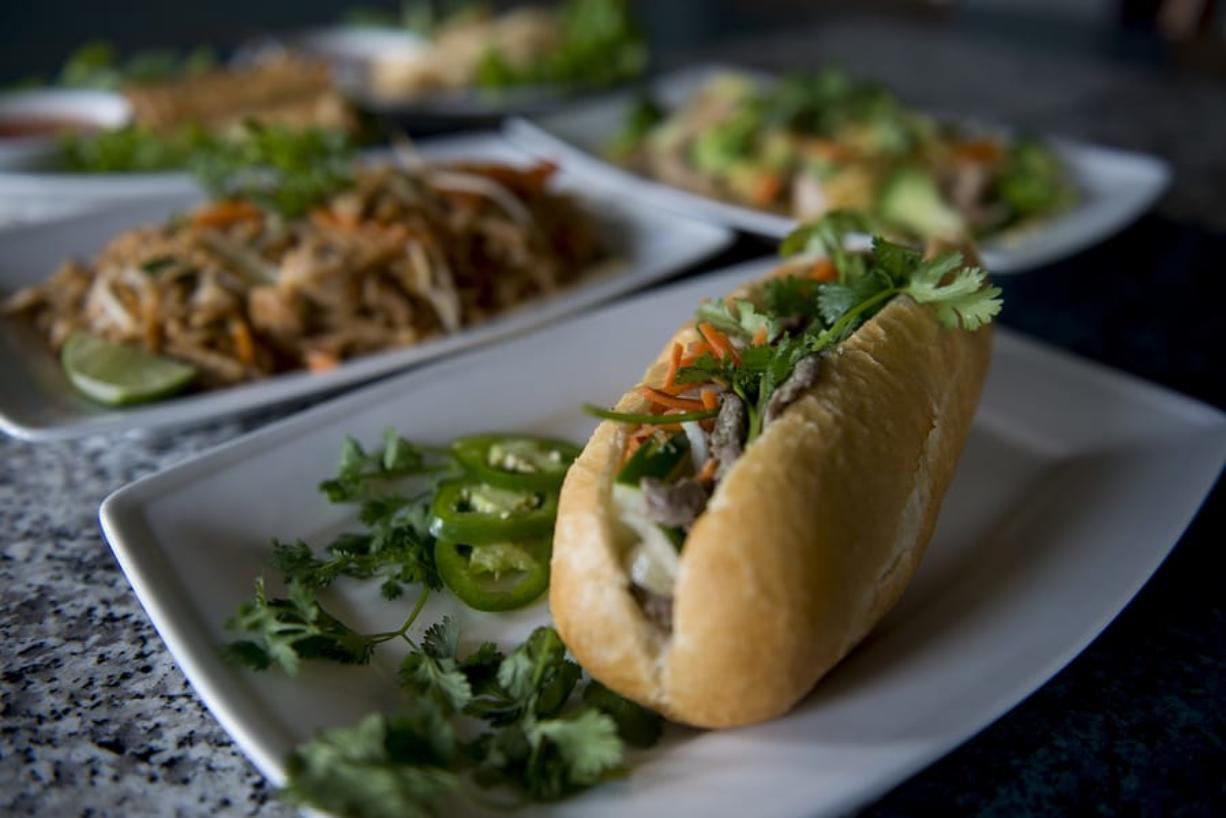 Banh mi with lemongrass beef, foreground, is served with other dishes at Pho Haven in Uptown Village on Friday afternoon, June 15, 2018.