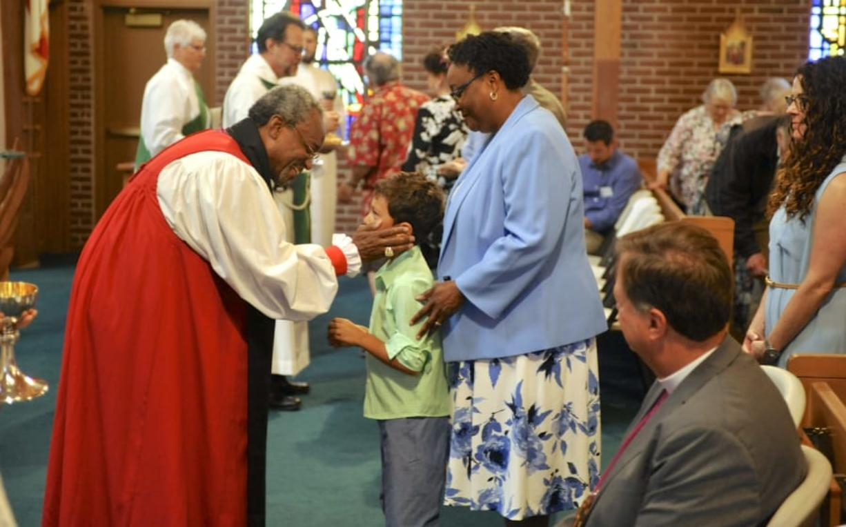 The Most Rev. Michael Curry, left, administers communion to Andrew Coxcollins and Lisa Collins at St. Luke's Episcopal Church in Vancouver on Sunday. Curry, as presiding bishop and primate of the Episcopal Church of the United States, is the leader of the church's clergy.