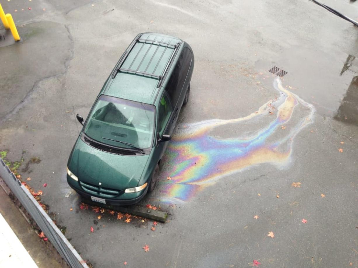 A leaking vehicle sends pollution down a parking lot storm drain. Leaky vehicles are a significant source of waterway pollution in Western Washington.