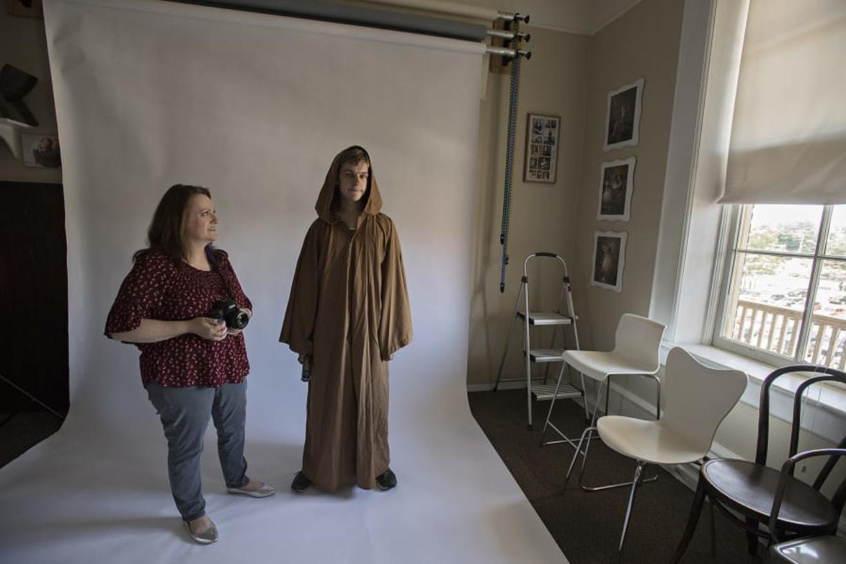 Tammy Fraley of Fraley Photography, left, shares a smile with Schuyler Smith of Vancouver as he is dressed as Obi-Wan Kenobi on Wednesday afternoon in downtown Vancouver. Fraley had previously taken Smith's portrait and the two reunited to have their photo taken together. Amanda Cowan/The Columbian
