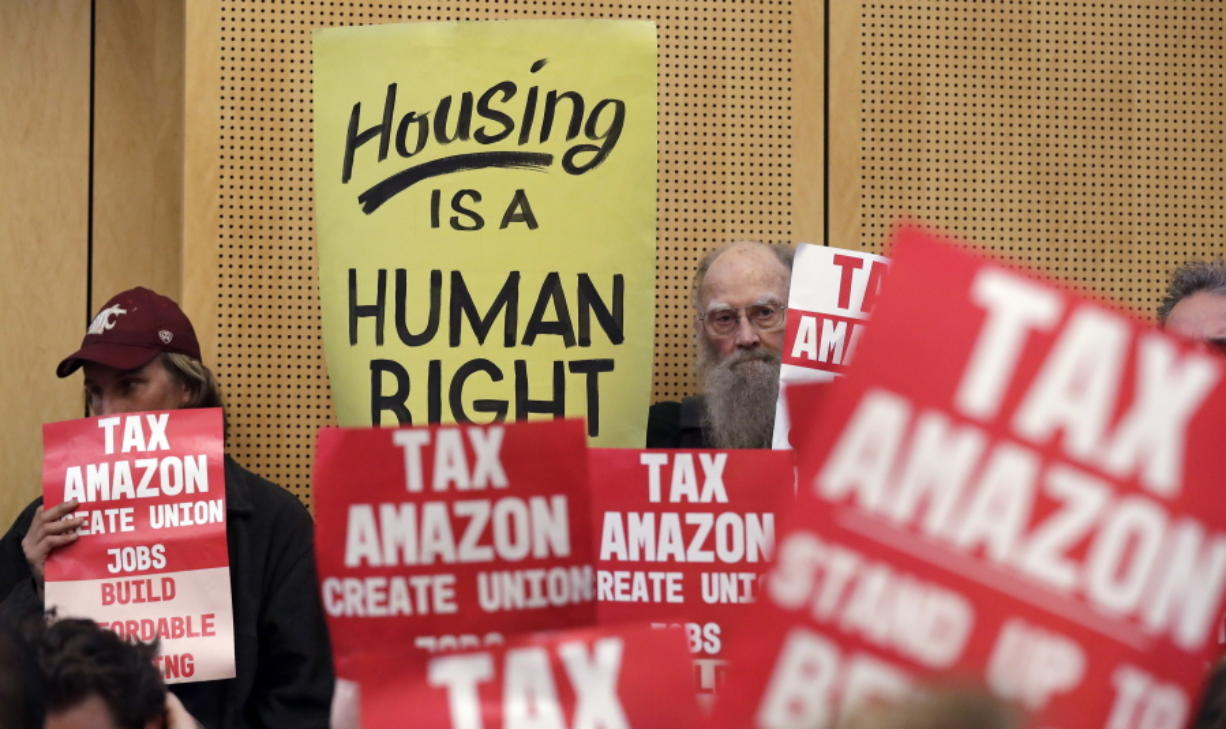 FILE - In this May 14, 2018 file photo, members of the public look on at a Seattle City Council before the council voted to approve a tax on large businesses such as Amazon and Starbucks to fight homelessness in Seattle. Amazon, Starbucks, Vulcan and a few dozen others have pledged more than $350,000 toward an effort to repeal Seattle's newly passed tax on large employers to combat homelessness.