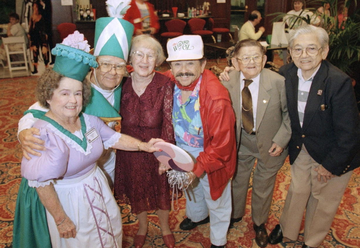 """FILE - In this Oct. 30, 1997 file photo, cast members from """"The Wizard of Oz,"""" from left, Margaret Pellegrini, Clarence Swensen, Ruth Duccini, Jerry Maren, Karl Slover and Mickey Carroll appear at the Culver Hotel in Culver City, Calif., where they stayed during the filming of the movie. Maren, the last surviving munchkin from the classic 1939 film """"The Wizard of Oz,"""" died on May 24, 2018, at a San Diego nursing home. He was 98. (AP Photo/Mark J."""